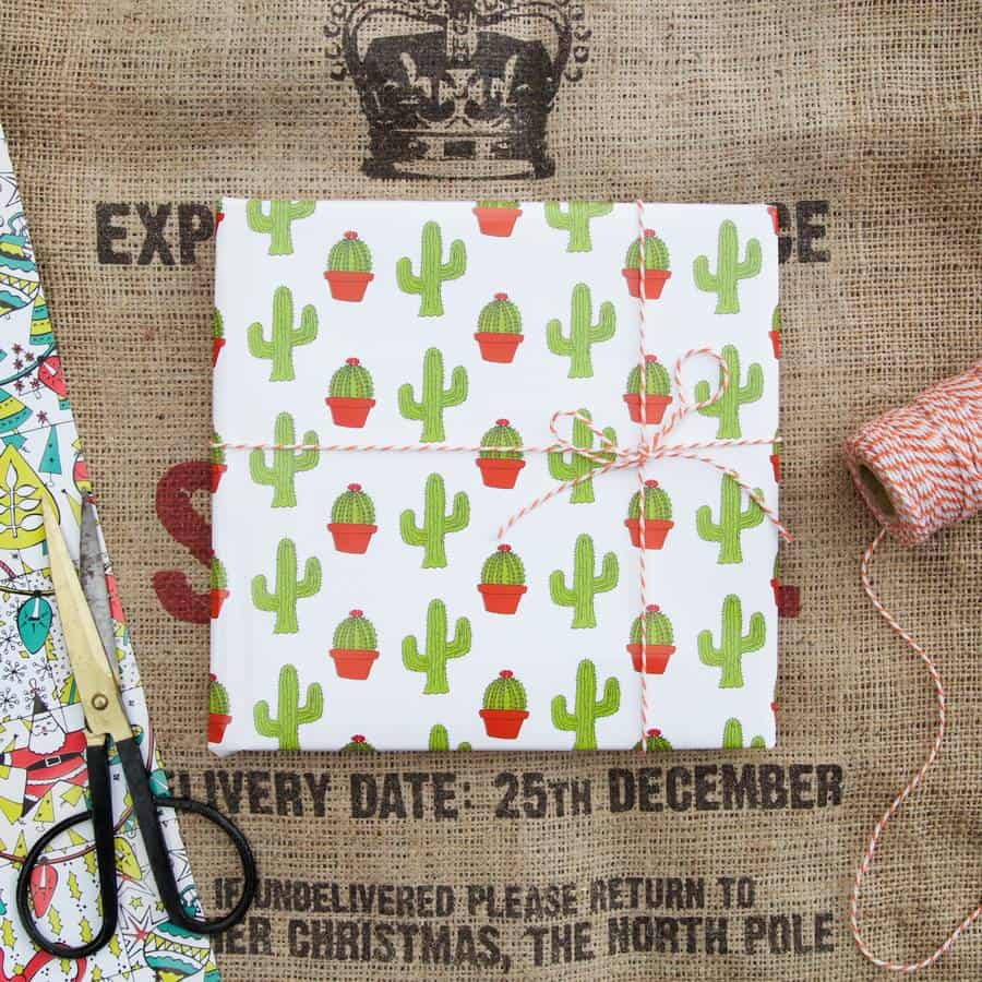 A present is wrapped in cactus wrapping paper and finished bound with red and white stripy string - Battersea Spanish
