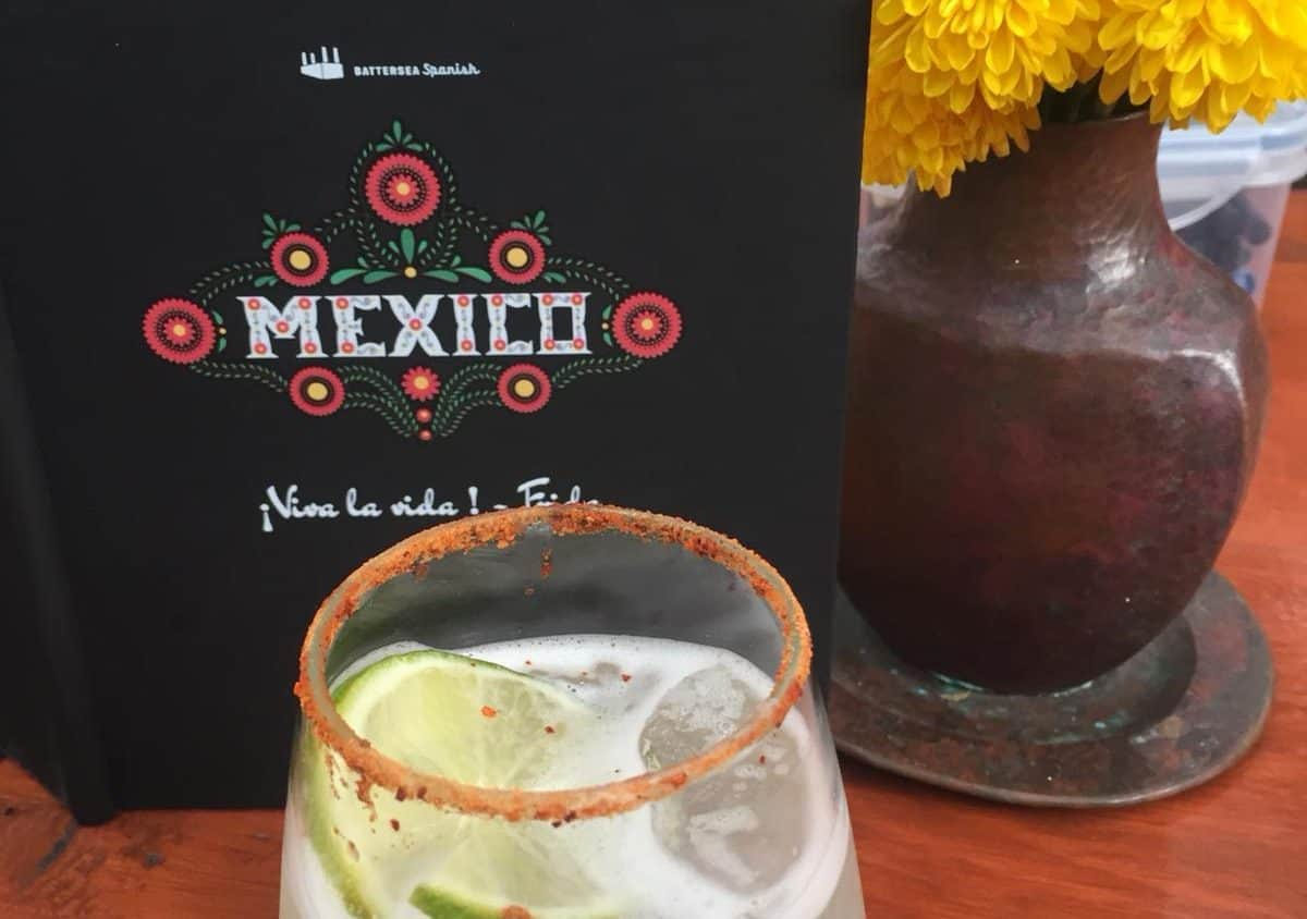 A margarita cocktail sits in front of a black book with traditionally styled calligraphy spelling Mexico and a copper vase with yellow petalled flowers