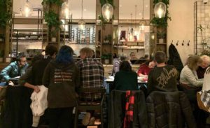 Peope sit at a high bar at a Spanish restaurant