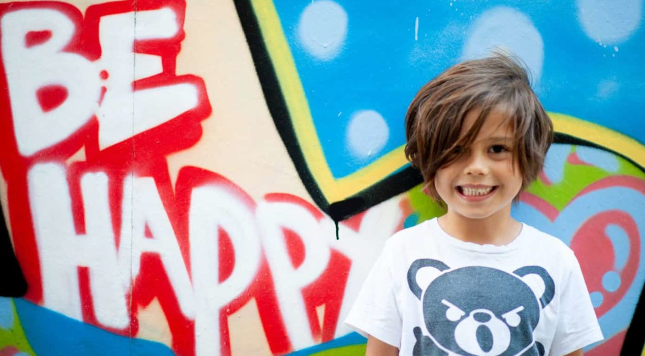 child standing in front of graffiti that says be happy